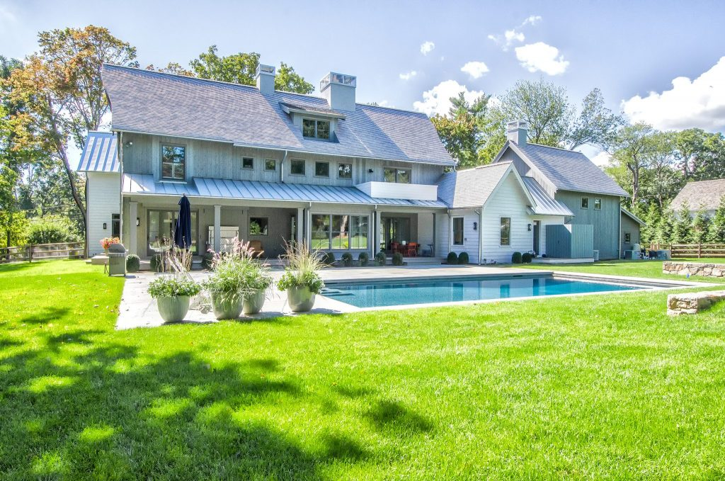 The backside of the farmhouse and white mother's study overlook the modern pool.