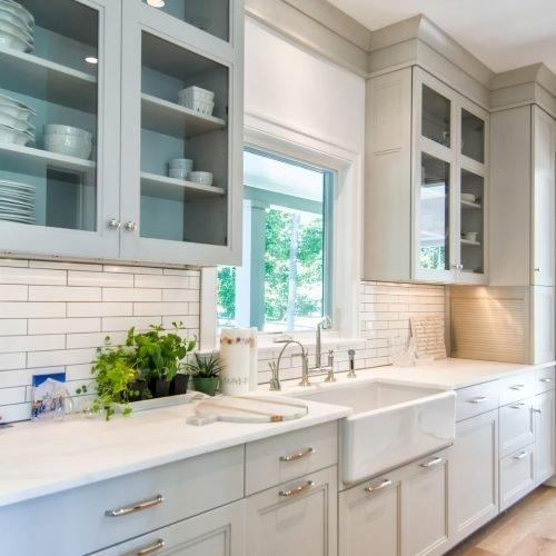 The farmhouse kitchen features porcelain farm sink, white oak floors and unique shaped subway tile.