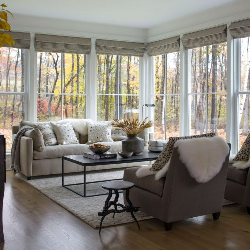 A secondary living space looks out into an aspen grove through large-paned windows.