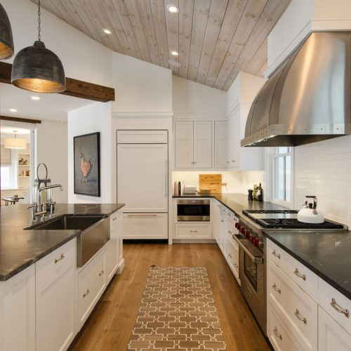 The modernist kitchen has a breakfast counter with an under-mounted farmhouse sink and slanted wood ceiling.