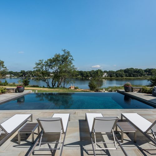 An infinity-edge pool blends visually with the tidal pond, which wraps around to Long Island Sound.