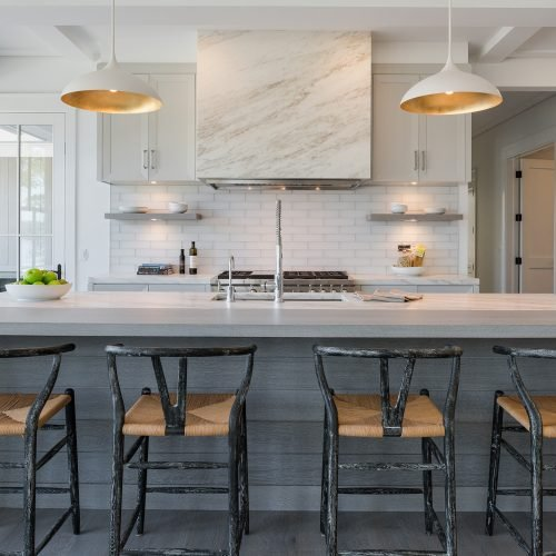 The wood and stone cooking island, range with a stone-wrapped hood and glass tile wall, floating, antique, white oak shelves, and modernized cabinetry with Scandinavian lighting.